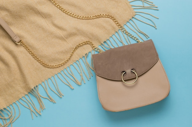 Borsa in pelle beige e tessuto beige su fondo blu. un accessorio da donna alla moda. accessori moda donna. lay piatto.