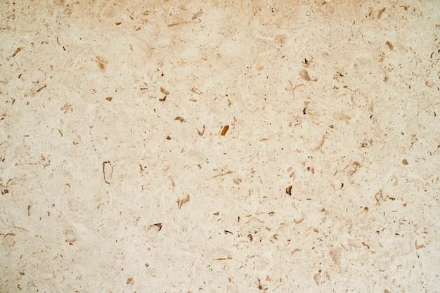 Struttura di marmo beige con il primo piano degli spruzzi