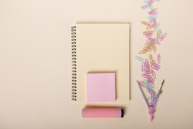 Un taccuino beige, un pennarello rosa, una bussola e graffette colorate sono splendidamente disposte su una luce...