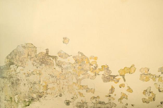 Parete verniciata beige. vernice incrinata nell'angolo. colore alterato con vernice scheggiata. copia spazio.