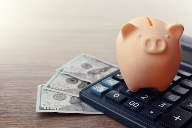Salvadanaio beige con banconote in dollari e calcolatrice su fondo in legno