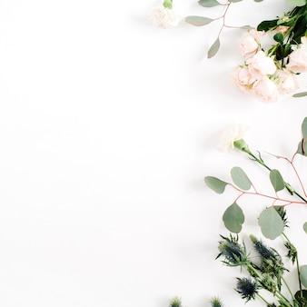 Fiori di rosa beige, fiore di eringium, rami di eucalipto su bianco