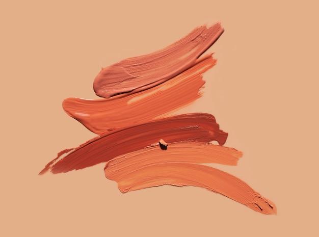 Sbavatura beige di struttura del fondo del rossetto della macchia isolata su beige