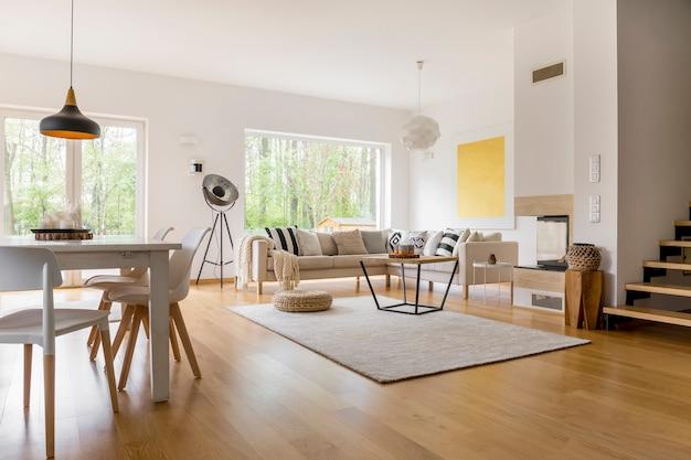 Divano beige con cuscini in soggiorno multifunzionale con tavolo da pranzo e sedie bianche