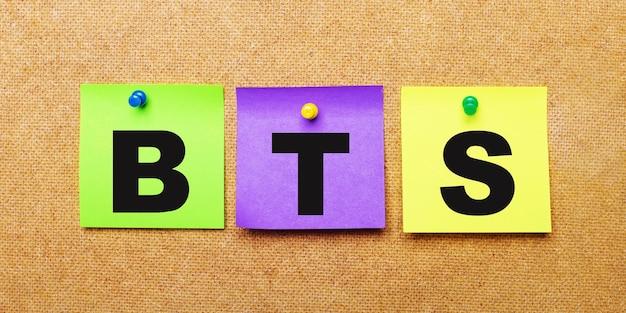 Su una superficie beige, adesivi multicolori per appunti con la parola bts