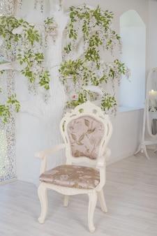 Sedia vintage beige nel lussuoso interno del soggiorno. stile soft focus. rustico. interno di un luminoso soggiorno scandinavo con fiori sul muro