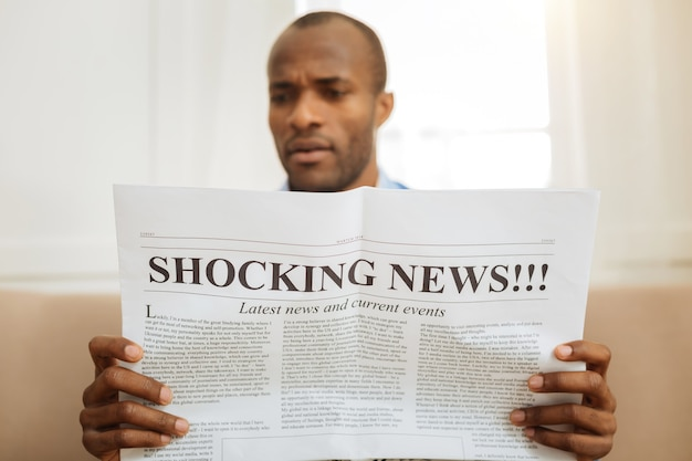 Stupirsi. uomo afroamericano seriamente stupito che tiene un giornale e legge notizie scioccanti mentre è seduto sul divano