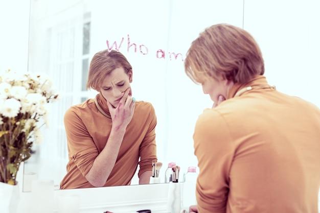 Essere estremamente infelice. un uomo queer di genere frustrato che allarga il rossetto sentendosi depresso per la sua identità