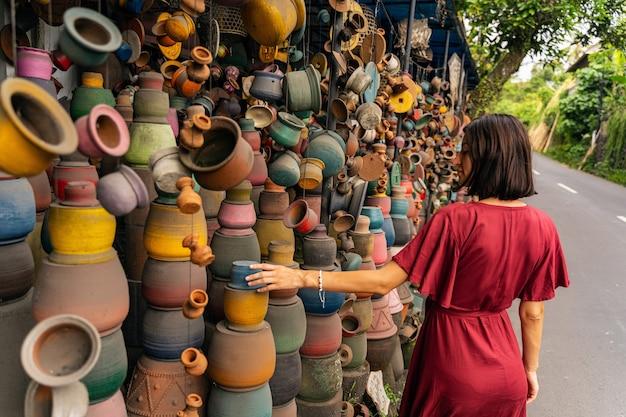Essere ispirato. piacevole ragazza bruna che gira la testa mentre guarda ceramiche colorate durante la passeggiata