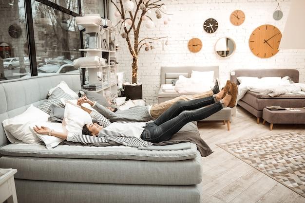 Essere interessati. coppia radiosa infantile che scherza mentre controlla la qualità del letto presentato nello showroom