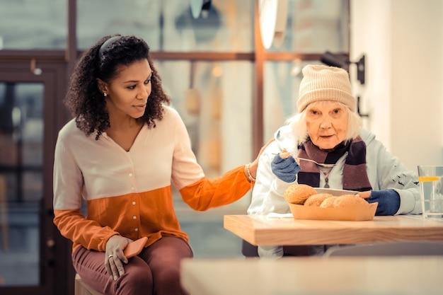 Essere fortunato. donna invecchiata triste che mangia un pasto gustoso mentre viene aiutata nella caffetteria