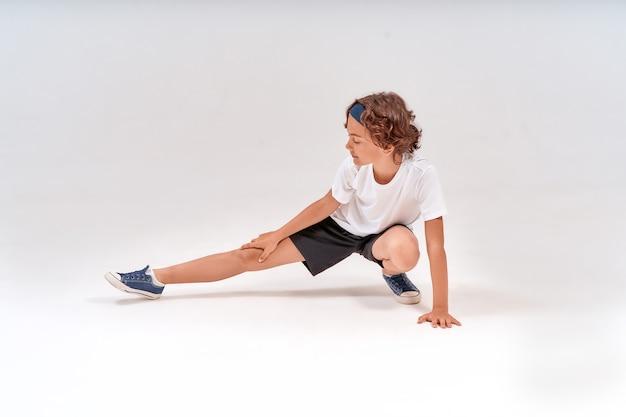 Essere fisicamente attivi per tutta la lunghezza di un adolescente caucasico in abiti sportivi che allungano il riscaldamento delle gambe