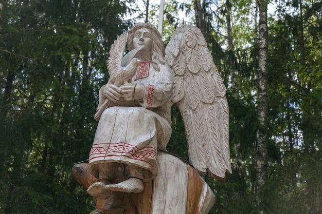 Sculture in legno nazionali bielorusse nella foresta. angelo di legno in abiti tradizionali bielorussi con un uccello tra le mani.