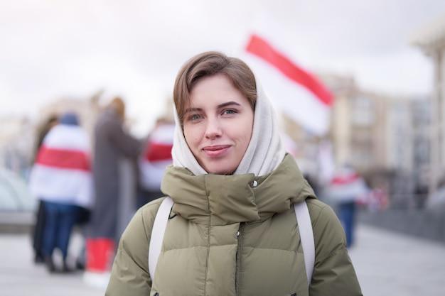 Donna bielorussa in piedi gruppo di manifestanti con bandiere bielorusse per protesta pacifica contro elezioni presidenziali illegali in bielorussia giovani adulti manifestanti