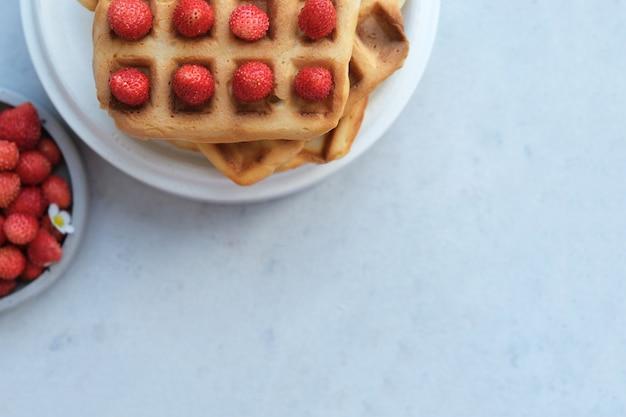 Waffle belgi o viennesi con piatto di fragole, snack da dessert, concetto di menu. copia spazio