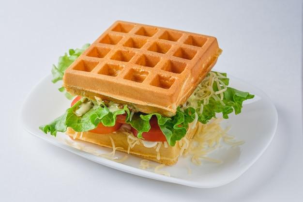 Sandwich di waffle belgi con pollo, lattuga, pomodoro, formaggio e maionese. piatto su un piatto bianco.