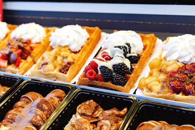 Cialde belghe cibo di strada con diversi condimenti frutta dolci panna montata.