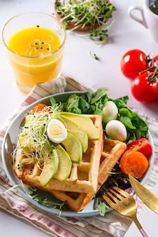 Cialde belghe con avocado, uova, micro verde e pomodori con succo d'arancia sul tavolo di marmo