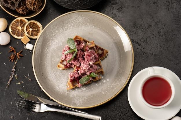 Cialde belghe con ricotta e marmellata di fragole, guarnite con foglie di menta per colazione. un dolce caldo salutare per tè o caffè.