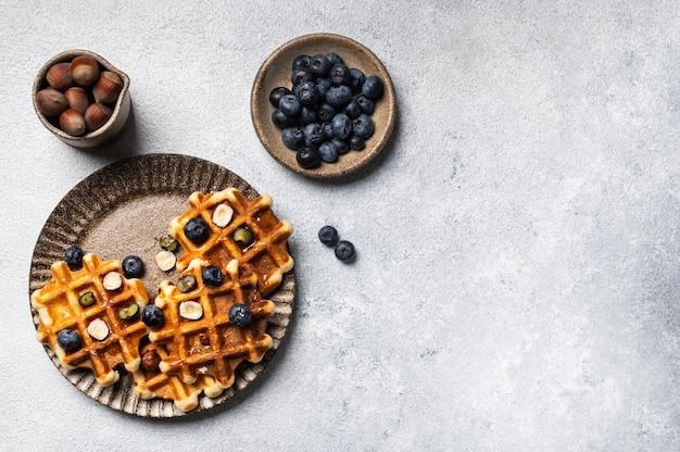 Cialde belghe con miele e frutti di bosco freschi mirtillo e nocciola su sfondo bianco. delizioso dessert. copia spazio. spazio per il testo. colazione deliziosa.