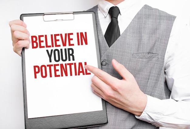 Credi nella tua potenziale iscrizione su un taccuino nelle mani di un uomo d'affari su uno sfondo grigio