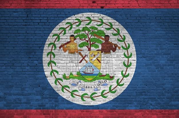 Bandiera del belize raffigurata nei colori della vernice sul vecchio muro di mattoni. insegna strutturata sul grande fondo della muratura del muro di mattoni