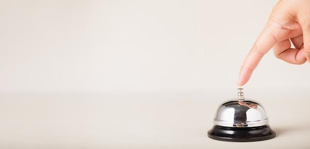 Servizio campanello al banco informazioni, chiamata campanello per servizio con la mano