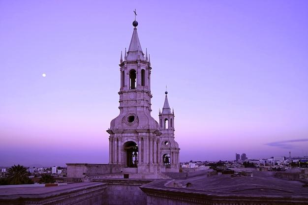 Il campanile della basilica cattedrale di arequipa sul cielo mattutino con la luna luminosa arequipa in perù