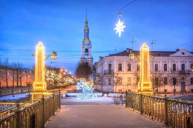 Il campanile della cattedrale di san nicola e l'angelo di capodanno a san pietroburgo sotto un cielo invernale blu