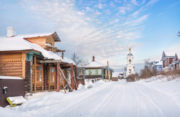 Il campanile della chiesa varvarinskaya e le case di legno sulla via varvarinskaya a plyos nella neve alla luce del sole invernale al tramonto.