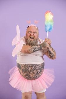 La persona obesa bellicosa in abito da fata attacca con un pennello per la polvere su sfondo viola