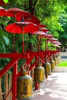 Campane sotto ombrellone rosso in un tempio buddista, thailandia