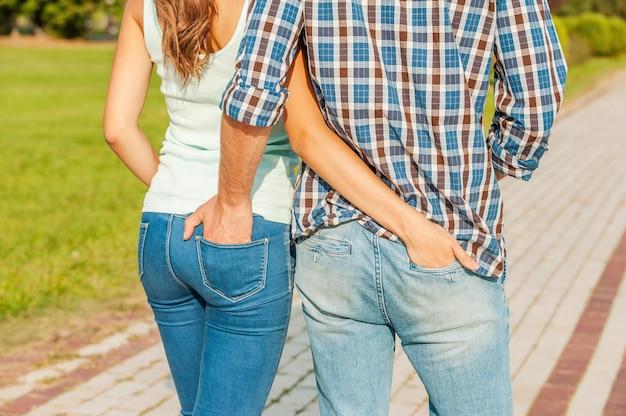 Appartenere l'uno all'altro. giovani coppie amorose che tengono le mani nelle tasche degli altri jeans mentre si cammina.