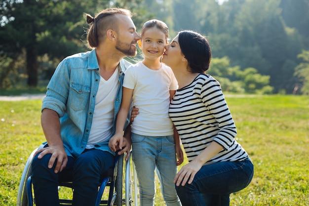 Figlio amato. gentile giovane madre e amorevole padre con disabilità, seduti su una sedia a rotelle, baciano la loro piccola figlia su entrambe le guance