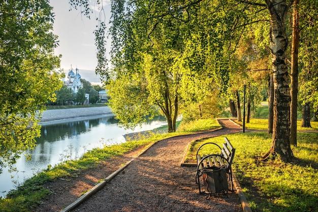Una panchina in un parco sulla riva del fiume e un tempio a vologda in una mattina di inizio estate