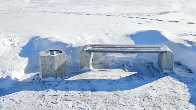 Panca sbucciata dalla neve in un luogo deserto in inverno senza persone in una giornata di sole
