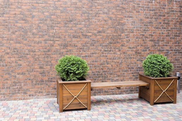 Panca per riposo e cespugli con dietro un muro di mattoni
