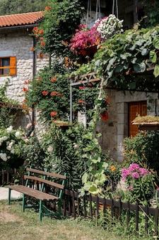 Una panchina nel giardino estivo vicino a un edificio in pietra con il tetto di tegole. umore estivo