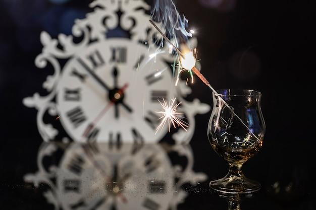 Candela bengala in un bicchiere contro l'orologio.