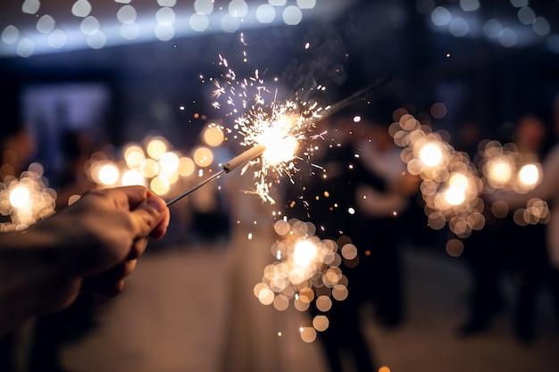Le luci del bengala nelle mani degli uomini si danno fuoco a vicenda sulle luci dell'albero di natale