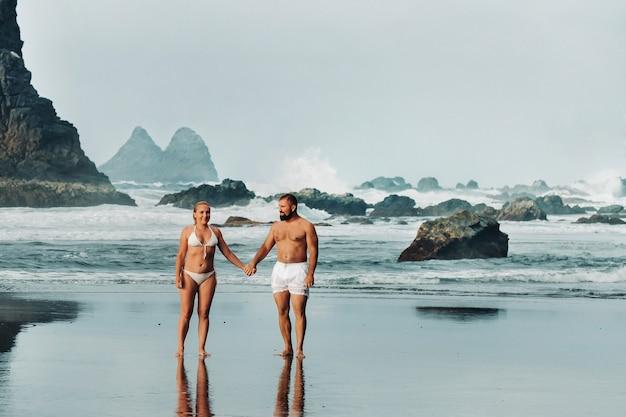 Benijo, tenerife, spagna : spiaggia di sabbia naturale. luogo popolare per gente del posto e turisti. le rocce vulcaniche fluttuano fuori dall'acqua turchese e le onde dolci e morbide che lavano la riva sabbiosa.
