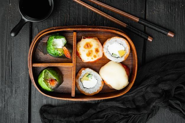 Insieme del rotolo di sushi di bento, sulla tavola di legno nera