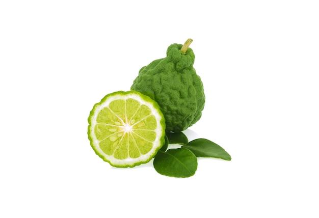 Frutta del bergamotto con tagliata a metà e foglia isolata su fondo bianco.