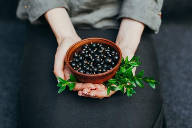 Bacche di ribes nei piatti in mani femminili. vitamine e concetto di mangiare sano