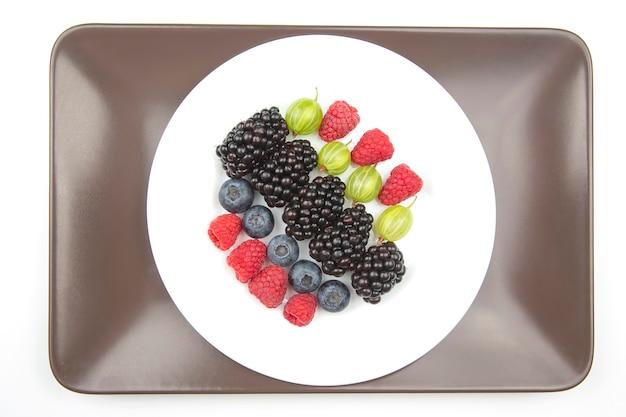 Lamponi, mirtilli, uva spina e more di bacche su un piatto bianco