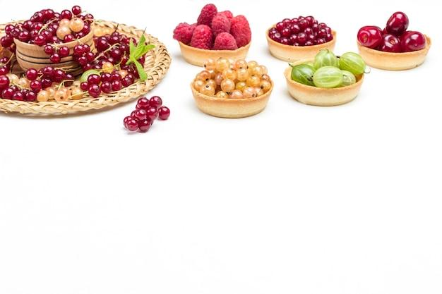 Bacche di ribes bianco e rosso sul piatto di vimini. tartellette di ciliegie, uva spina e ribes. copia spazio. sfondo bianco. vista dall'alto