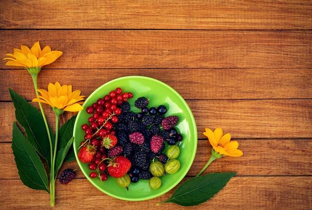 Mix di frutti di bosco su un piattino verde con fiori gialli su uno sfondo di legno