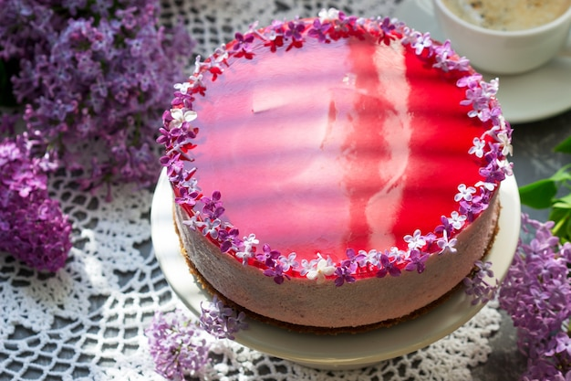 Una mousse ai frutti di bosco con base di cioccolato e gelatina di succo, decorata con fiori lilla, servita con caffè.