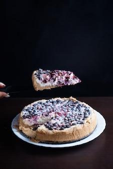 Torta ai frutti di bosco con le ciliegie ribes in una ciotola di freschi e fumanti tagli caldi un pezzo di sfondo è sfocato