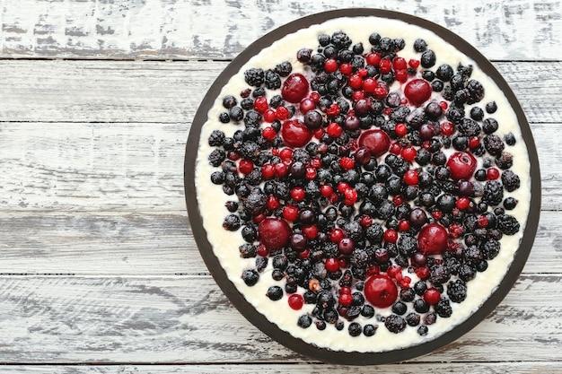 Torta di frutti di bosco con ciliegia, ribes, mora, mirtillo bianco sulla tavola di legno. vista dall'alto della torta di formaggio con lo spazio della copia.